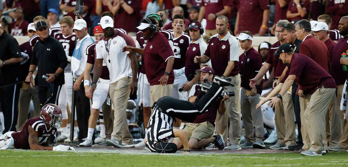 A referee was knocked over during a play along the sideline during the fourth quarter of a college football game at Kyle Field, Saturday, Oct. 8, 2016 in College Station.