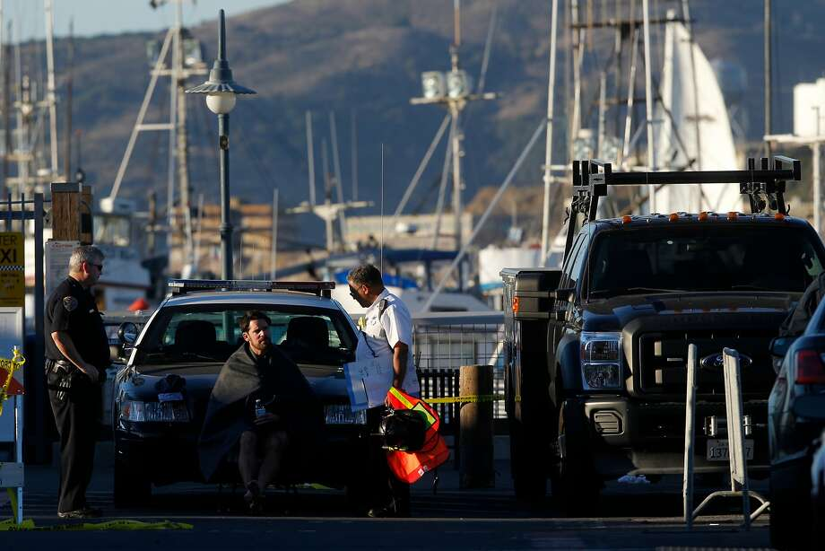 A man sits with a blanket near the scene following an overturned boat by pier 45 on  Saturday, Oct. 8, 2016 in San Fransico , Calif. Photo: Gabriella Angotti-Jones, The Chronicle