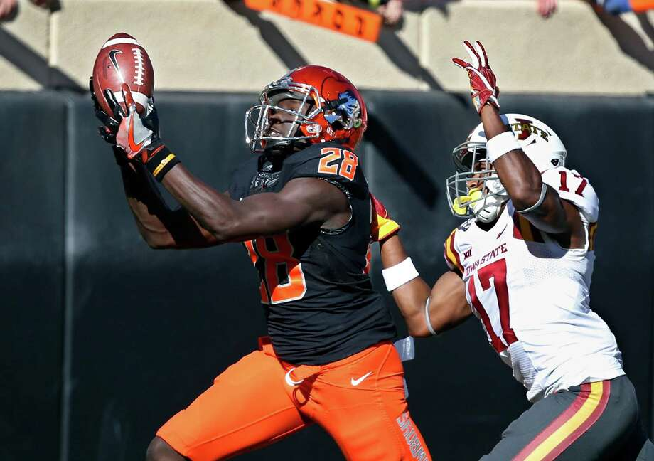 Oklahoma State wide receiver James Washington, left, catches a pass in front of Iowa State defensive back Jomal Wiltz on Saturday at Stillwater, Okla. Photo: Sue Ogrocki, STF / AP2016