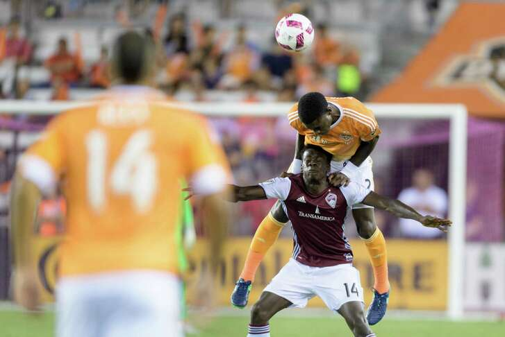 Jalil Anibaba of the Dynamo goes over the top to win a header with the Rapids' Dominique Badji.