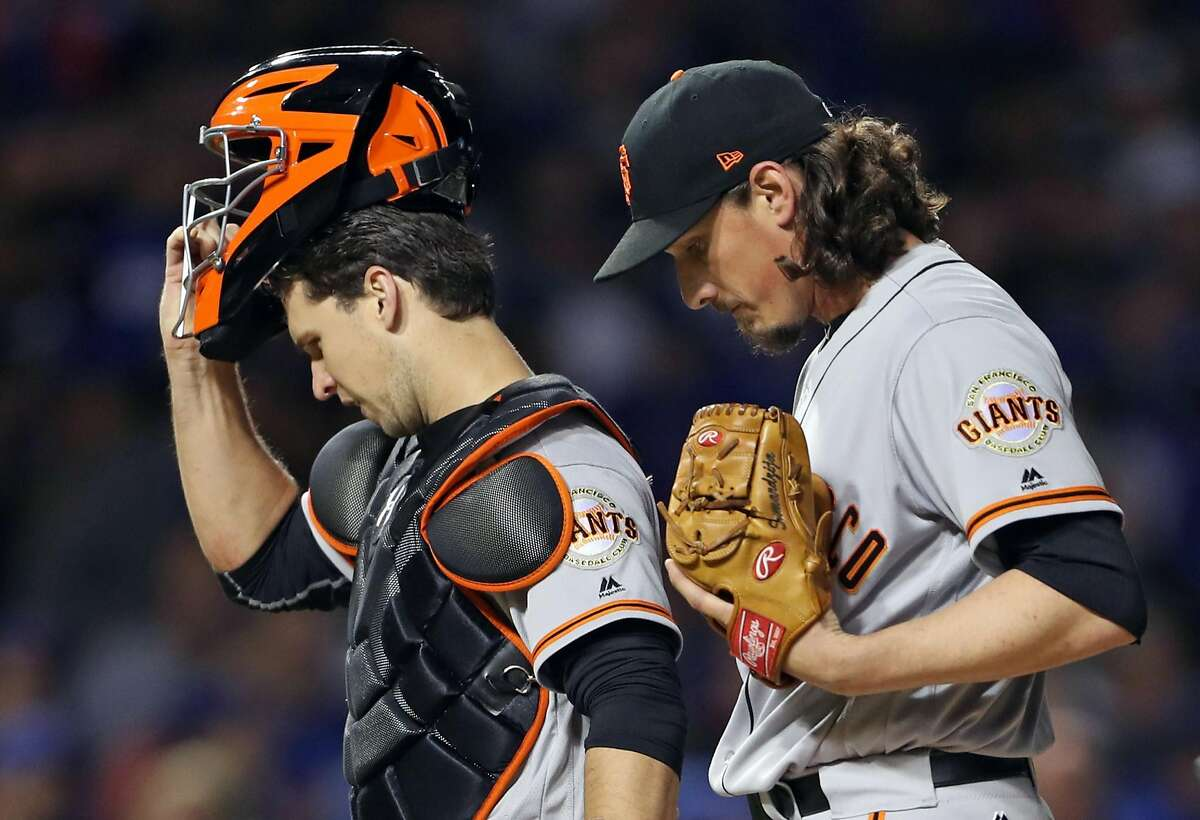 San Francisco Giants' Jeff Samardzija and Buster Posey react during Chicago Cubs' 3-run 2nd inning during Game 2 of the National League Division Series at Wrigley Field in Chicago. IL, on Saturday, October 8, 2016.
