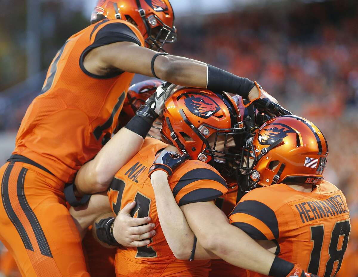 Oregon State running back Ryan Nall, center, is mobbed by teammates after scoring a touchdown during the first half of an NCAA college football game against California, in Corvallis, Ore., on Saturday, Oct. 8, 2016. (AP Photo/Timothy J. Gonzalez)