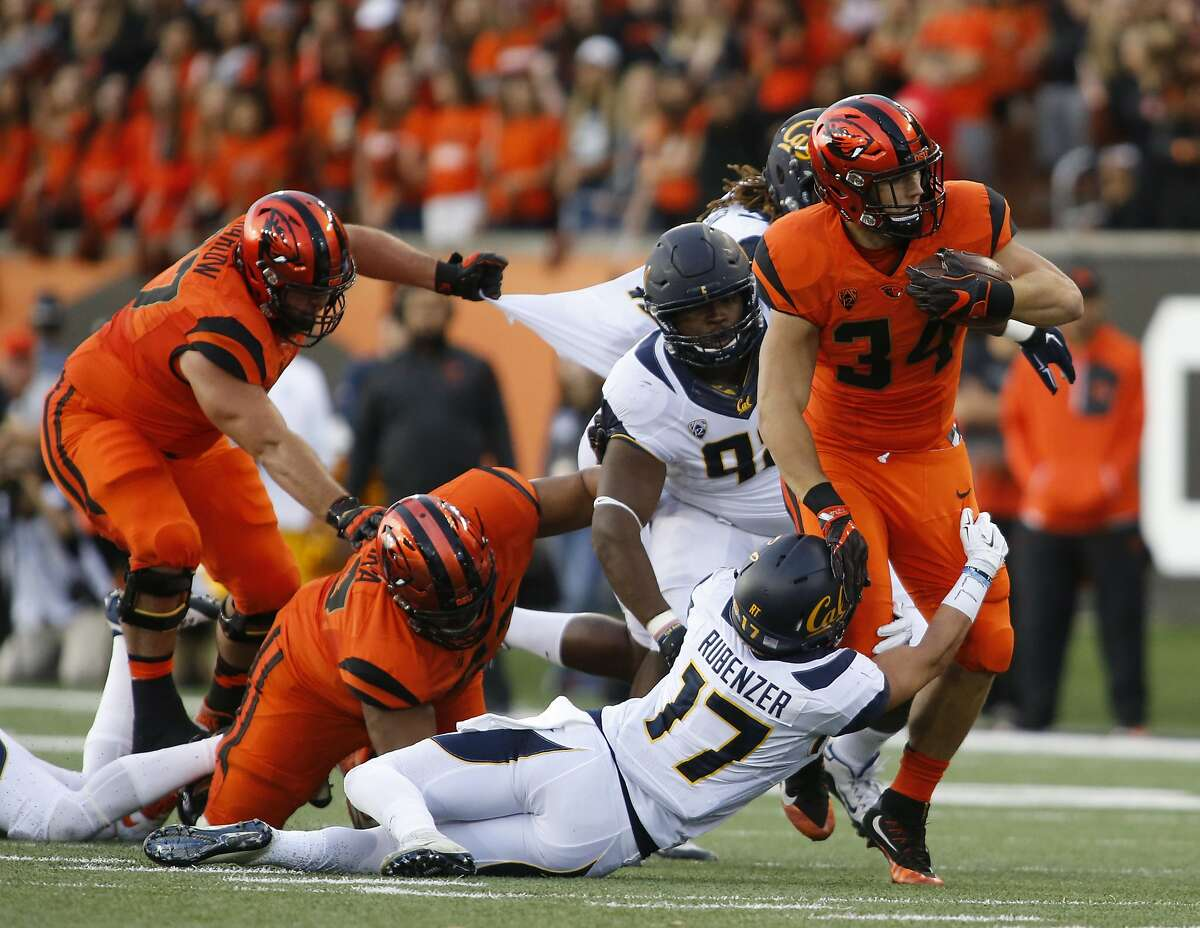 Oregon State running back Ryan Nall (34) tries to break out of the grip of California's Luke Rubenzer (17) during the first half of an NCAA college football game in Corvallis, Ore., on Saturday, Oct. 8, 2016. (AP Photo/Timothy J. Gonzalez)