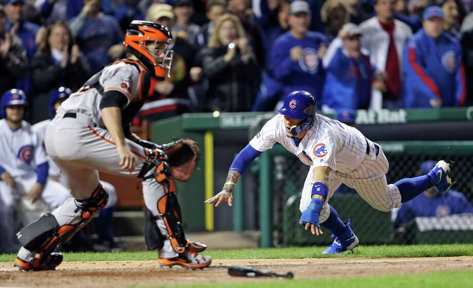 San Francisco Giants' Buster Posey awaits the throw as Chicago Cubs' Javier Baez scores on Kyle Hendricks' 2-run single in 2nd inning during Game 2 of the National League Division Series at Wrigley Field in Chicago. IL, on Saturday, October 8, 2016. Photo: Scott Strazzante, Staff Photographer / **MANDATORY CREDIT FOR PHOTOG AND SF CHRONICLE/NO SALES/MAGS OUT/TV