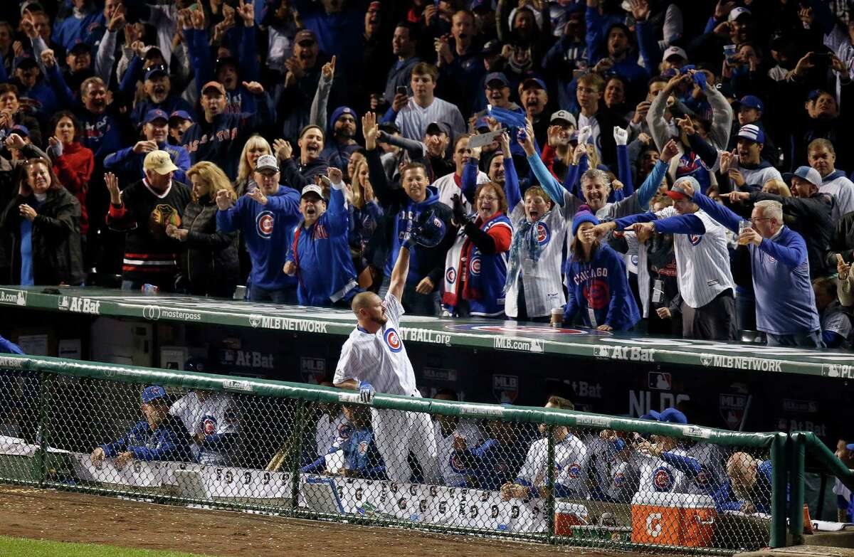 Cubs reliever Travis Wood receives a curtain call from the crowd at Wrigley Field after hitting a solo home run in the fourth inning Saturday night, becoming the first reliever to hit a postseason homer since 1924.
