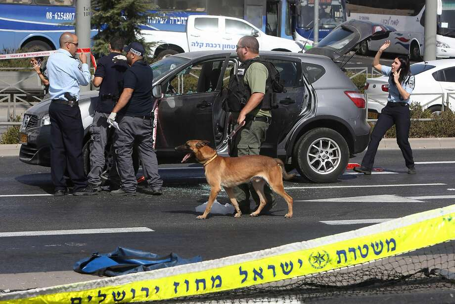 Forensic police collect evidence from a car belonging to a victim of a shooting attack near the Israeli police headquarters in Jerusalem. The gunman was shot dead by Israeli officers. Photo: MENAHEM KAHANA, AFP/Getty Images