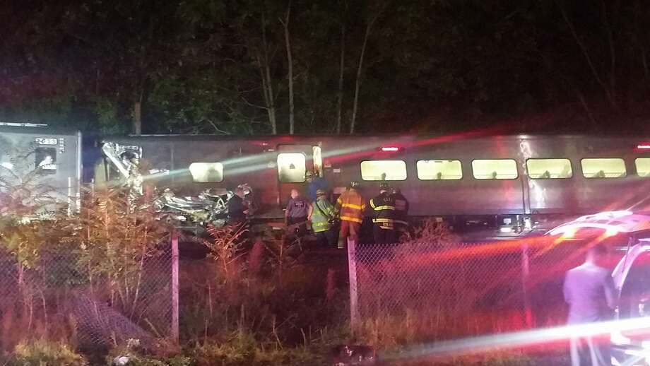 In this photo provided by Sarah Qamar rescue personnel look at a Long Island Railroad train that derailed near New Hyde Park, N.Y., Saturday, Oct. 8, 2016.  The commuter train derailed east of New York City after it hit a work train on the tracks. A spokesman for the Long Island Rail Road says the eastbound train derailed east of New Hyde Park just after 9 p.m. Saturday. A spokeswoman for the Nassau County Police Department says there are 50 to 100 injuries, none of them life-threatening. (Sarah Qamar via AP) Photo: Sarah Qamar, Associated Press