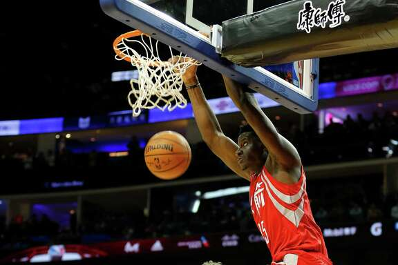 Houston Rockets Clint Capela, right, leaps onto the ring as he scores while New Orleans Pelicans Omer Asik watches during their preseason NBA game in Shanghai, China, Sunday, October, 9, 2016. (AP Photo)