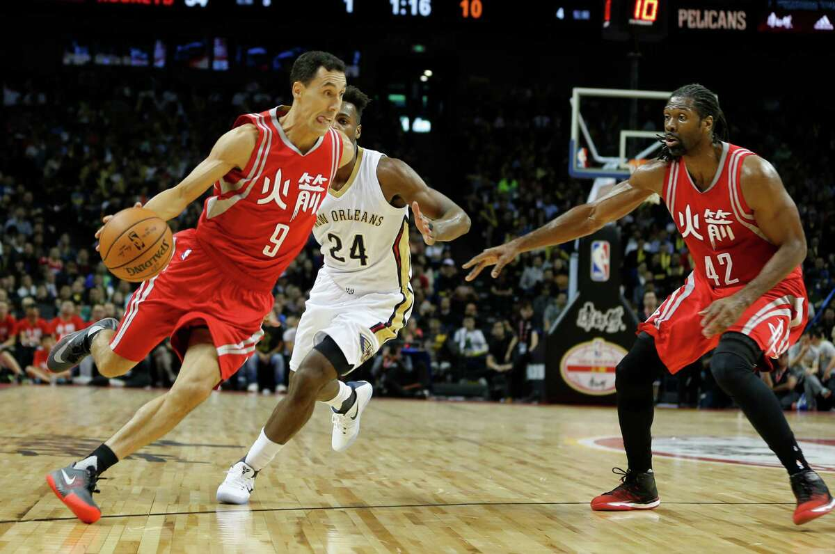Houston Rockets Pablo Prigioni, dribbles the ball past New Orleans Pelicans Buddy Hield, centre, as teammate Nene Hilario, right, watches during their preseason NBA game in Shanghai, China, Sunday, October, 9, 2016. (AP Photo)