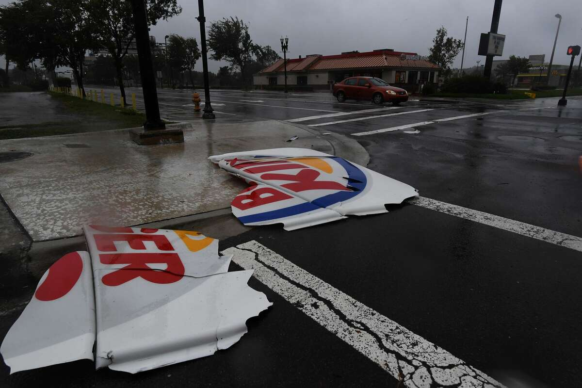 A car drive past a broken Burger King sign on a street in Jacksonville, Florida, on October 7, 2016, as hurricane Matthew passes the area. Hurricane Matthew lashed NASA's rocket launch facility at Cape Canaveral on Friday, causing power outages and damaging roofs as heavy winds battered the Florida coast, the US space agency said. / AFP / JEWEL SAMAD (Photo credit should read JEWEL SAMAD/AFP/Getty Images)