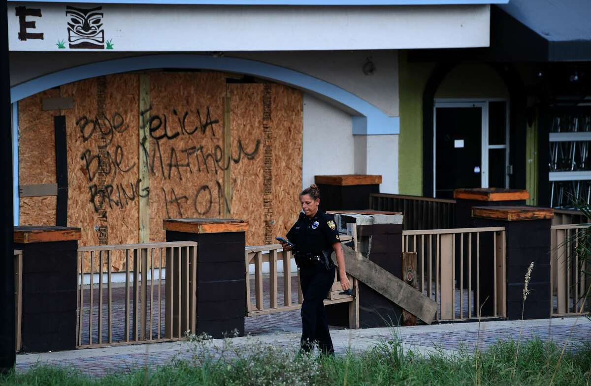 A police officer walks past a closed store in Jacksonville Beach, Florida, on October 8, 2016, after Hurricane Matthew passed the area. A weakened Hurricane Matthew churned just off the coast of the US states of Georgia and South Carolina Saturday, threatening deadly floods after leaving more than a million people without power in Florida and claiming five lives. The full scale of the devastation in hurricane-hit rural Haiti became clear as the death toll surged past 400, three days after Hurricane Matthew leveled huge swaths of the country's south. / AFP / Jewel SAMAD (Photo credit should read JEWEL SAMAD/AFP/Getty Images)