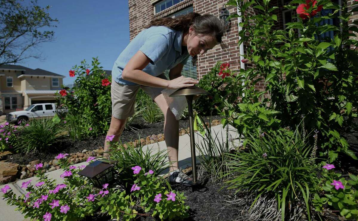 Mariya Kostova puts a pathway light into her client's flower bed Wednesday, Sept. 28, 2016, in Fulshear. Kostova started her outdoor lighting company in 2012 and left her corporate job in fall 2015 and became full-time with her own company. (Yi-Chin Lee / Houston Chronicle )