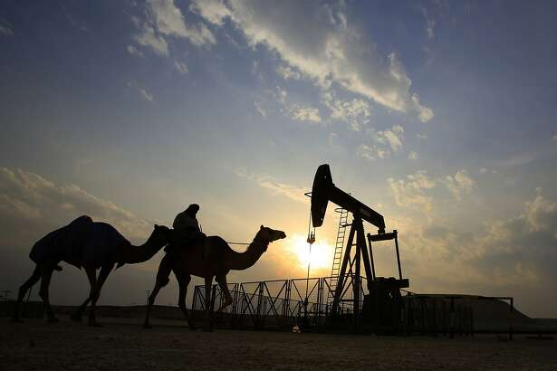 FILE- In this Sunday, Dec. 20, 2015 file photo, a man rides a camel through the desert oil field and winter camping area of Sakhir, Bahrain. OPEC nations have agreed in theory that they need to reduce their production to help boost global oil prices during a meeting in Algeria, but a major disagreement between regional rivals Saudi Arabia and Iran still may derail any cut. (AP Photo/Hasan Jamali, File)
