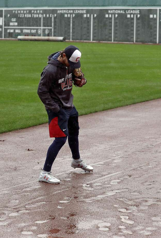 Cleveland Indians starting pitcher Josh Tomlin checks footing on the rain-soaked warning track in the outfield at Fenway Park on Sunday. Game 3 was rained out. Photo: Charles Krupa, Associated Press