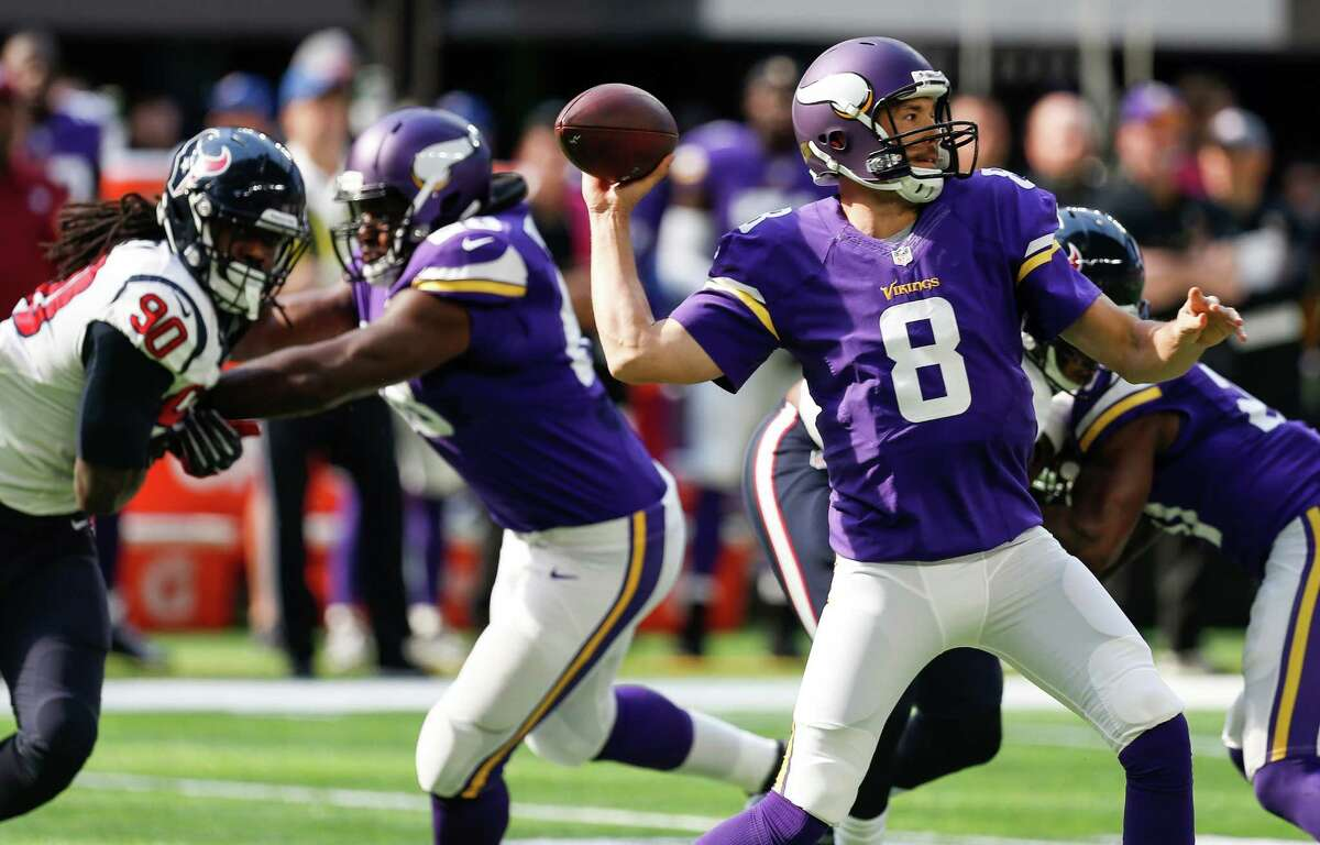 Minnesota Vikings quarterback Sam Bradford (8) throws a pass with Houston Texans defensive end Jadeveon Clowney (90) rushing from the left during the first quarter of an NFL football game at U.S. Bank Stadium on Sunday, Oct. 9, 2016, in Minneapolis.