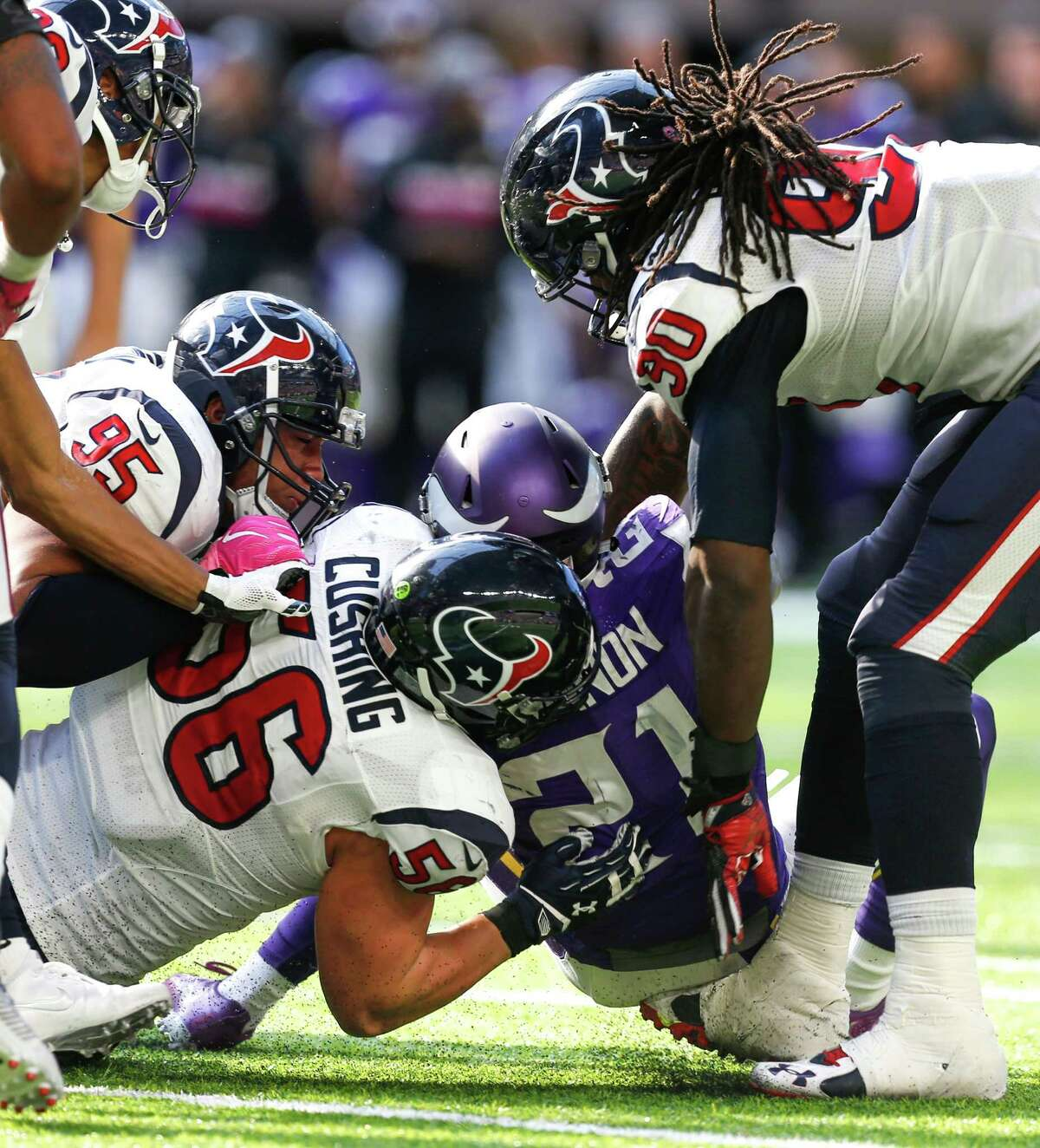 Minnesota Vikings running back Jerick McKinnon (21) is tackled by Houston Texans inside linebacker Brian Cushing (56) and defensive end Jadeveon Clowney (90) during the fourth quarter of an NFL football game at U.S. Bank Stadium on Sunday, Oct. 9, 2016, in Minneapolis.