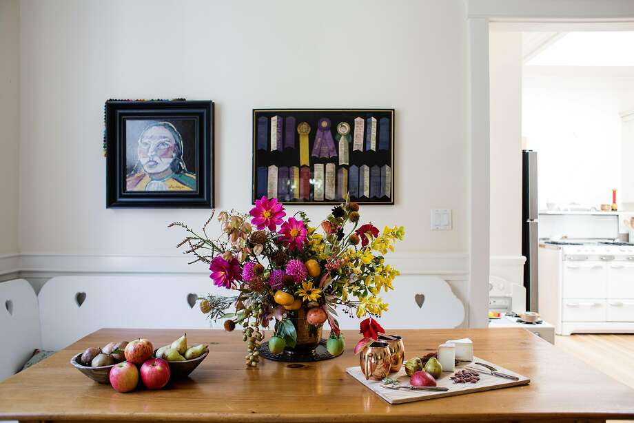 Julia Lake combines natural elements and heirloom finds with this Ira Yeager painting (left), framed dog show ribbons and a flower arrangement with bowls of fall fruit. Photo: Talia Herman