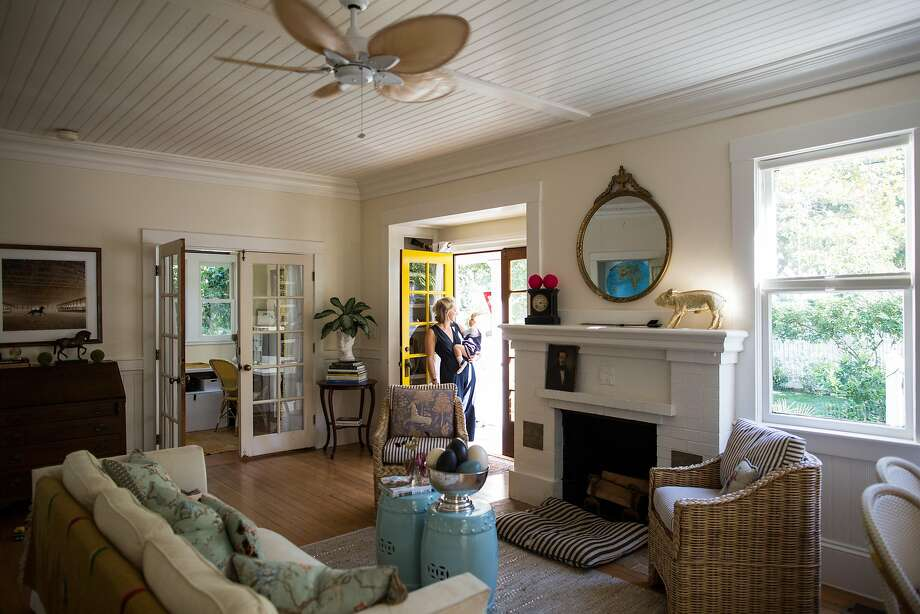 Julia Lake holds her son in the entryway of her home. She painted the French doors a radiant yellow and placed a Hello Sunshine welcome mat on the stoop. Inside, she chose a neutral envelope color that doesn't compete with the decor. Photo: Talia Herman