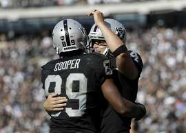 Oakland Raiders wide receiver Amari Cooper (89) and quarterback Derek Carr celebrate after connecting on a touchdown pass against the San Diego Chargers during the second half of an NFL football game in Oakland, Calif., Sunday, Oct. 9, 2016. (AP Photo/Marcio Jose Sanchez)