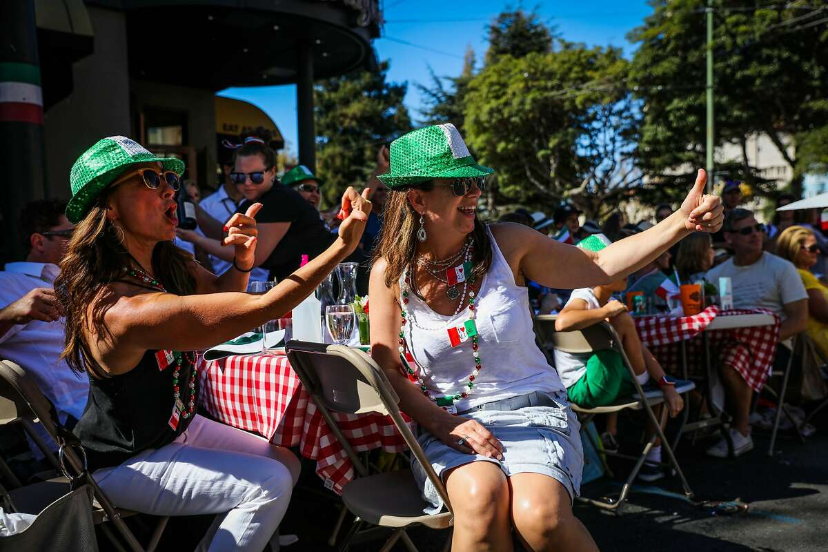 (l-r) Lyte Paulson and Sheila Ogden cheer as a float passes by during the Italian Heritage parade, in San Francisco, California, on Sunday, Oct. 9, 2016.