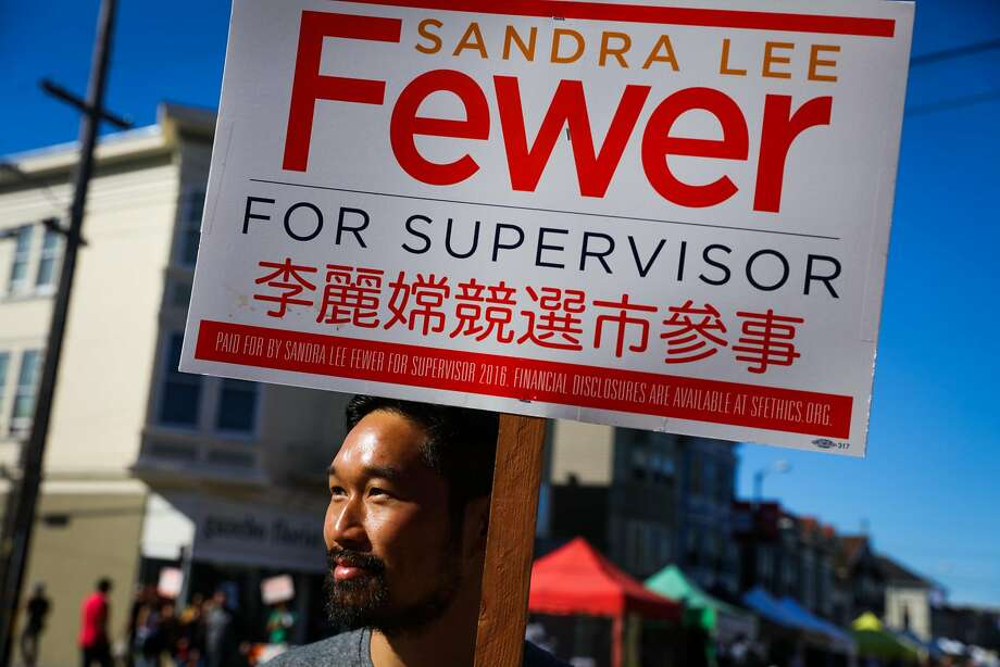 Carson Lau holds up a sign in support of Sandra Fewer, who is running for District One supervisor. Photo: Gabrielle Lurie, The Chronicle