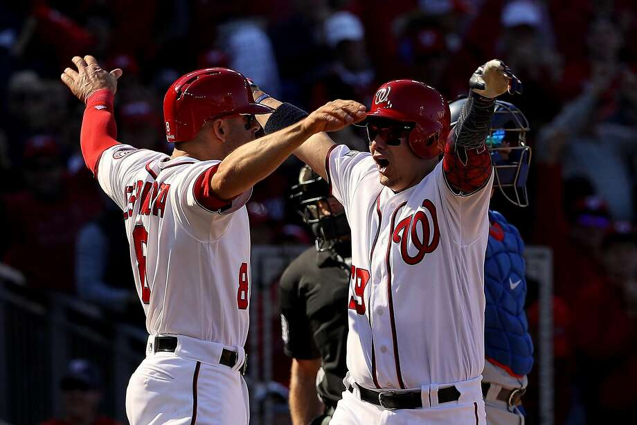 Danny Espinosa (left) greets Jose Lobaton after the catcher's three-run home run gave the Nationals the lead in Game 2. Photo: Patrick Smith, Getty Images