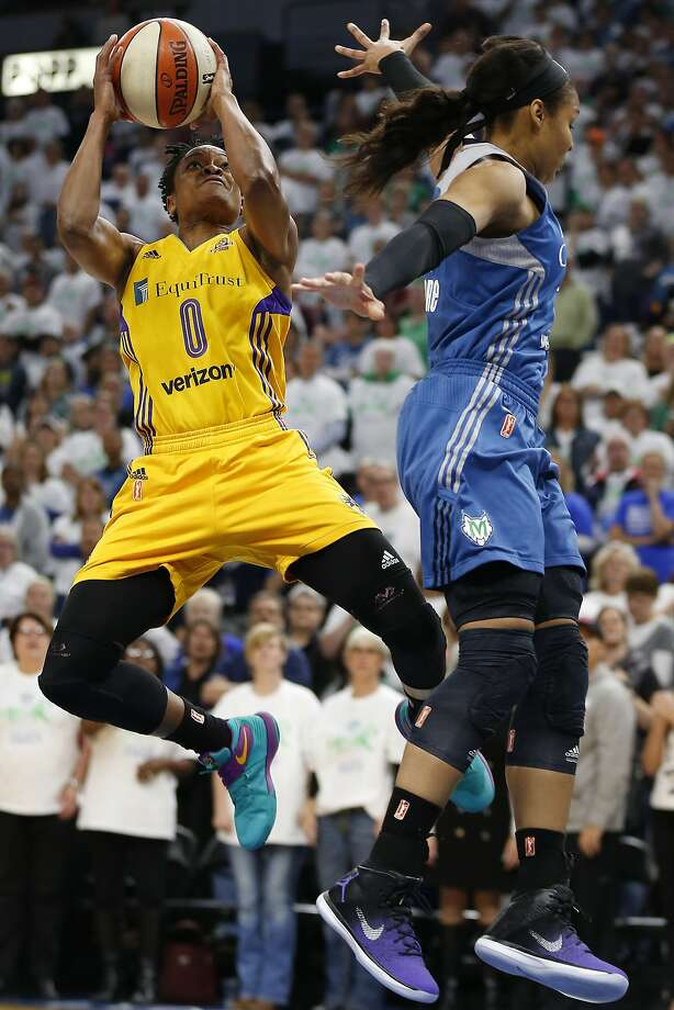 Los Angeles' Alana Beard shoots past the defense of Minnesota's Maya Moore in the first half in Minneapolis. Photo: Stacy Bengs, Associated Press