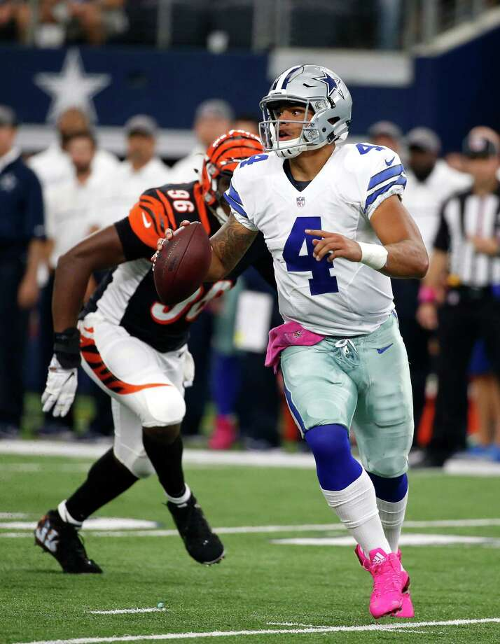 Dallas Cowboys quarterback Dak Prescott (4) scrambles out of the pocket under pressure from Cincinnati Bengals defensive end Carlos Dunlap (96) in the first half of an NFL football game, Sunday, Oct. 9, 2016, in Arlington, Texas. Photo: Michael Ainsworth, AP / FR171389 AP