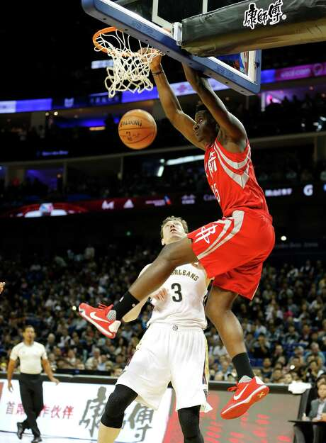 The Pelicans' Omer Asik can do little but watch as the Rockets' Clint Capela puts the finishing touch on an alley-oop dunk during Sunday's preseason game at Shanghai. Photo: STR / Copyright 2016 The Associated Press. All rights reserved.