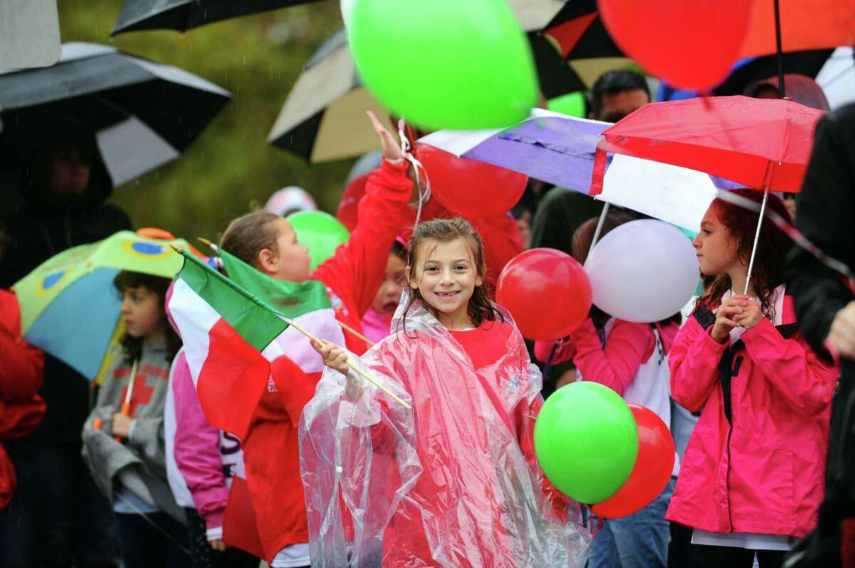 Anne Leydon, 8, smiles as she walks in the Columbus Day Parade in downtown Stamford on Sunday.