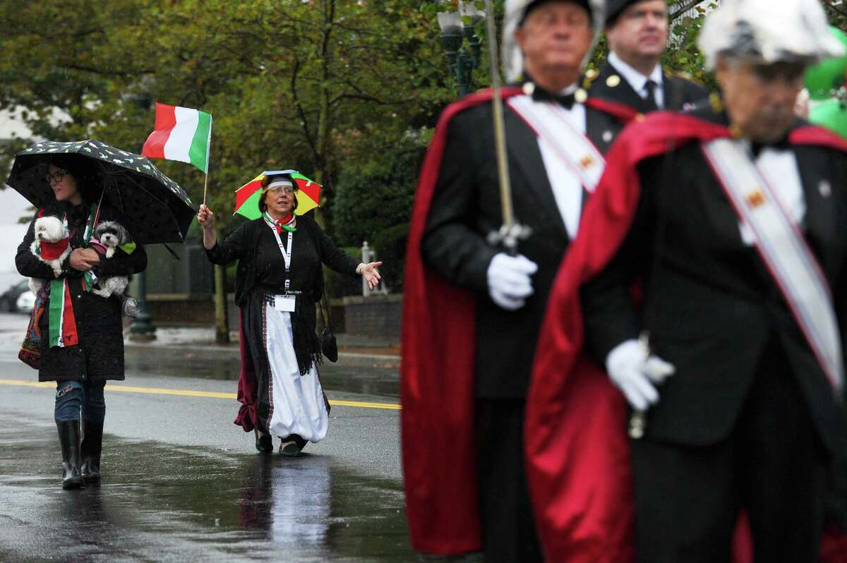 Parade chairwoman Lorraine Santora Olsen, second from left, waves an Italian flag during the parade.