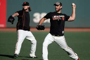 Madison Bumgarner (40) warms up with Steven Okert, rear, during an optional practice at AT&T Park in San Francisco, Calif., on Sunday, October 9, 2016.  The Giants take the field tomorrow in game 3 of the NLDS against the Chicago Cubs.