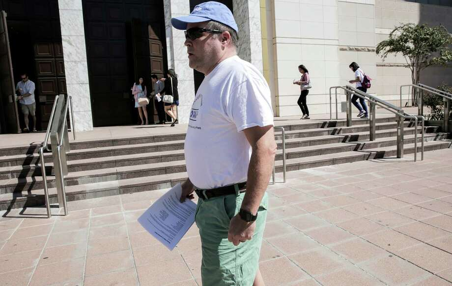 Michael Norris, who was abused by a Catholic priest as a child, passes out fliers outside the Co-Cathedral of the Sacred Heart on Sunday for the Survivors Network of those Abused by Priests.  Photo: Elizabeth Conley, Staff / © 2016 Houston Chronicle