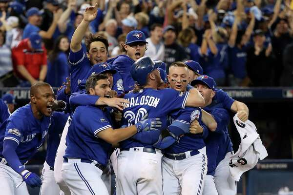 TORONTO, ON - OCTOBER 9: Josh Donaldson #20 of the Toronto Blue Jays celebrates with teammates after the Toronto Blue Jays defeated the Texas Rangers 7-6 in ten innings during game three of the American League Division Series at Rogers Centre on October 9, 2016 in Toronto, Canada.
