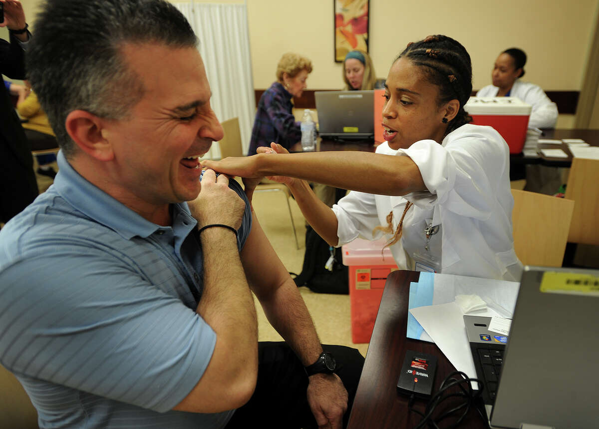 Food and nutrition supervisor Christopher Batsu, left, reacts as he gets his flu shot from nurse Catherine Adams, LPN, during a free flu shot clinic for hospital staff at Bridgeport Hospital in Bridgeport, Conn. on Thursday, October 6, 2016. All Yale-New Haven Hospitals, which includes Bridgeport Hospital, require staff to be immunized by December 1.