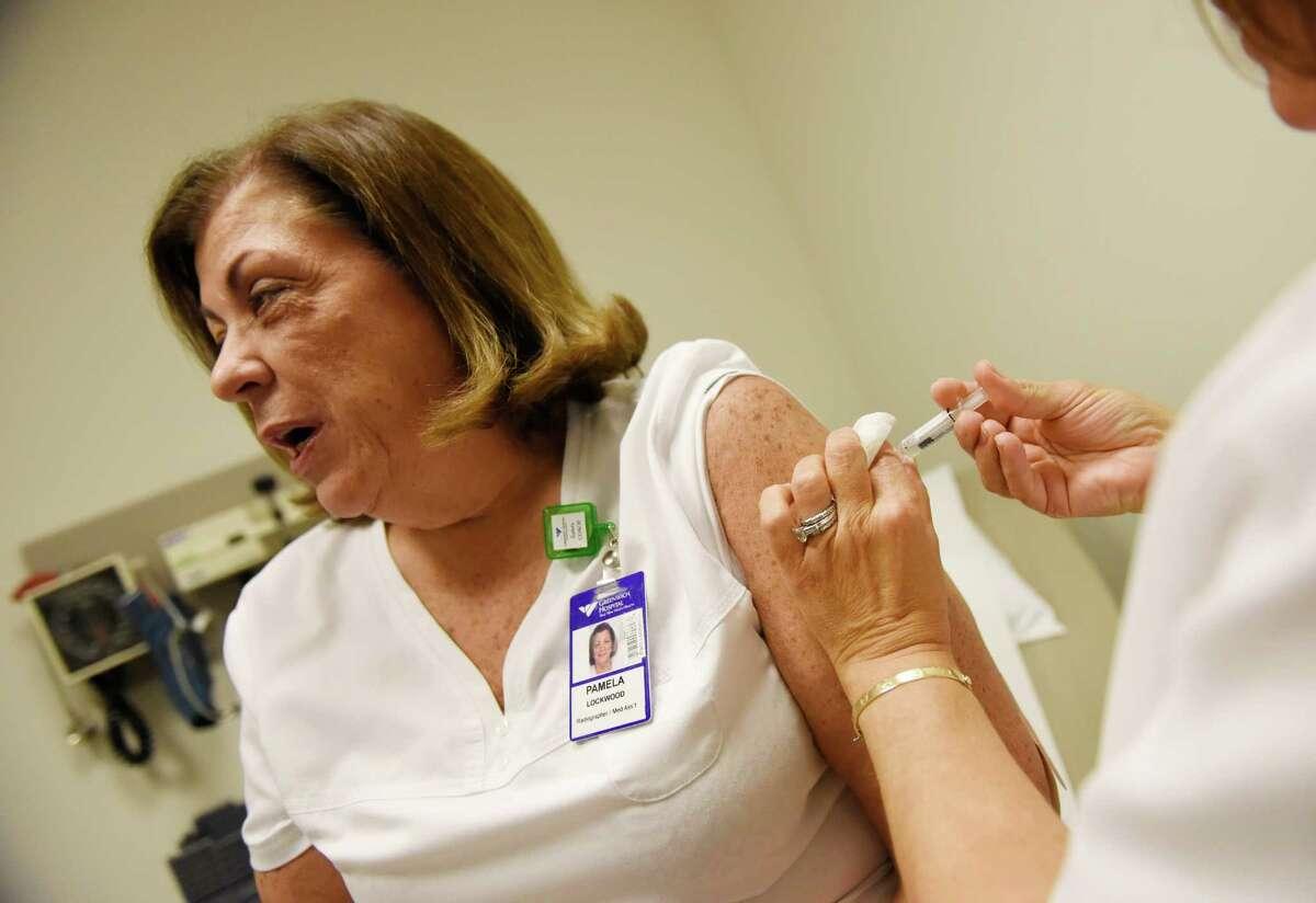 Karen Herbster, R.N., administers a flu shot to hospital employee Occupational Health Medical Assistant Pamela Lockwood at Greenwich Hospital in Greenwich.