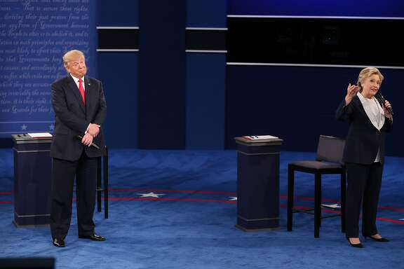 Donald Trump, 2016 Republican presidential nominee, gestures as Hillary Clinton, 2016 Democratic presidential nominee, speaks during the second U.S. presidential debate at Washington University in St. Louis, Missouri, U.S., on Sunday, Oct. 9, 2016. As has become tradition, the second debate will resemble a town hall meeting, with the candidates free to sit or roam the stage instead of standing behind podiums, while members of the audience -- uncommitted voters, screened by the Gallup Organization -- will ask half the questions. Photographer: Daniel Acker/Bloomberg