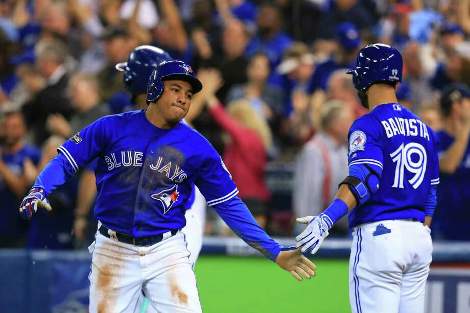 TORONTO, ON - OCTOBER 9: Ezequiel Carrera #3 of the Toronto Blue Jays celebrates with teammate Jose Bautista #19 after scoring off of an RBI double hit by Josh Donaldson #20 (not pictured) in the third inning against the Texas Rangers during game three of the American League Division Series at Rogers Centre on October 9, 2016 in Toronto, Canada. (Photo by Vaughn Ridley/Getty Images) Photo: Vaughn Ridley, Stringer / 2016 Getty Images