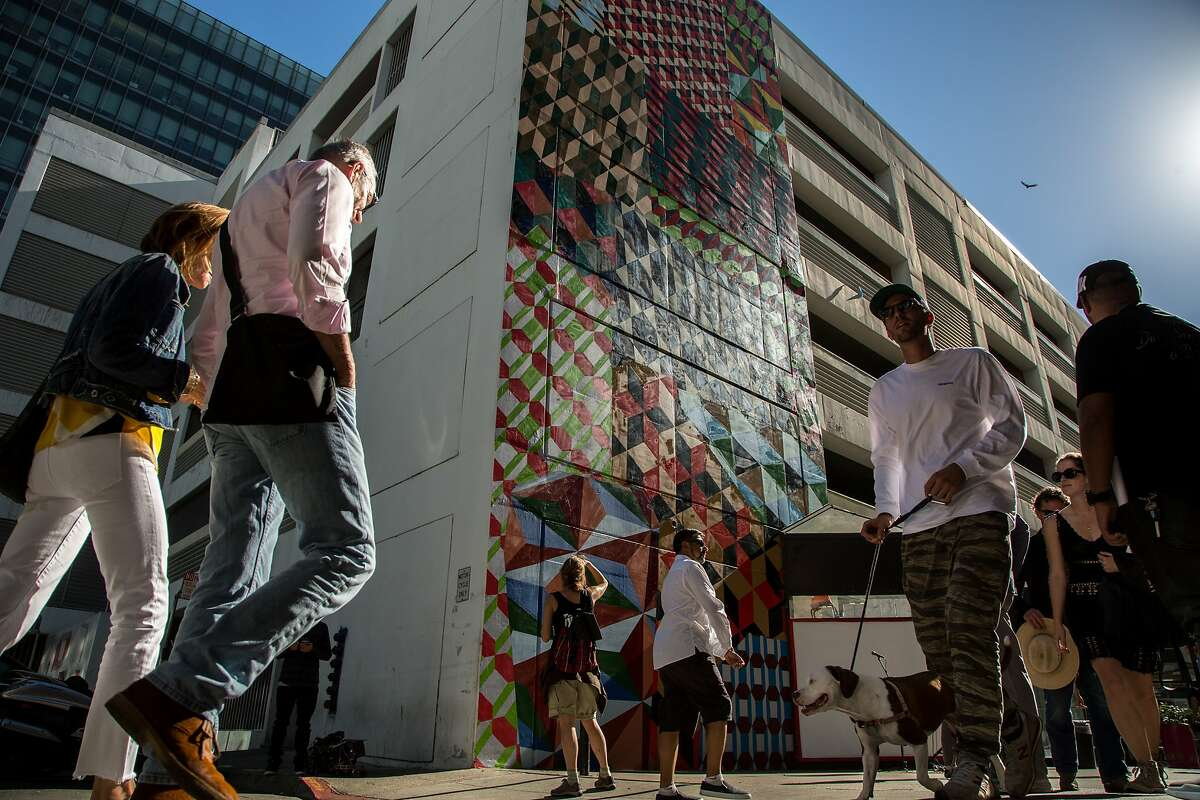People check out the new murals during the Sites Unseen opening ceremony, Sunday, Oct. 9, 2016 in San Francisco, California. Sites Unseen is a public-art organization embarking on an ambitious program to install public art all around the South of Market neighborhood. Seven murals are on the Moscone parking garage just down from SFMOMA.