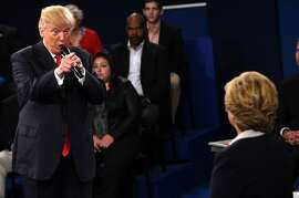TOPSHOT - US Democratic Presidential nominee Hillary Clinton (R) and Republican Presidential nominee Donald Trump participate a town hall debate against Republican nominee Donald Trump at Washington University in St. Louis, Missouri, on October 9, 2016.  / AFP PHOTO / POOL / SAUL LOEBSAUL LOEB/AFP/Getty Images
