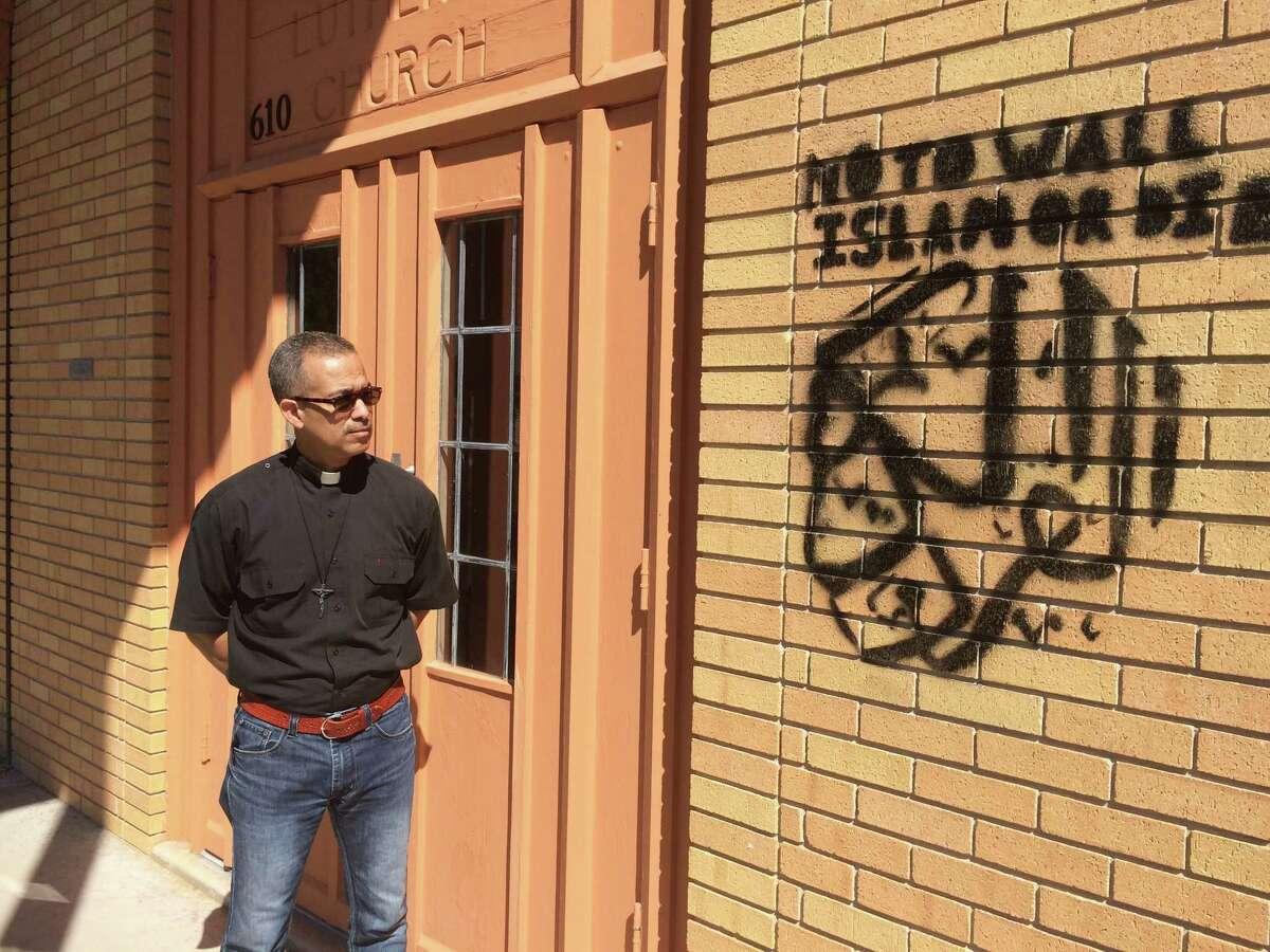 Pastor Eric Miletti (left) looks at graffiti Monday October 10, 2016 that was painted on a wall at Gethsemane Lutheran Church at 610 Avalon. Police are investigating the incident.