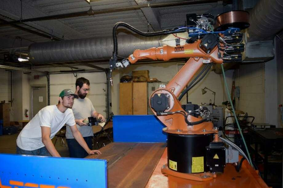 TSTC in Waco welding technology students (left) Taylor Otte of Lexington and (right) Rhett Fuller of Cedar Park learn about a new welding robot donated by ARC Specialties in Houston. Photo: Submitted Photo