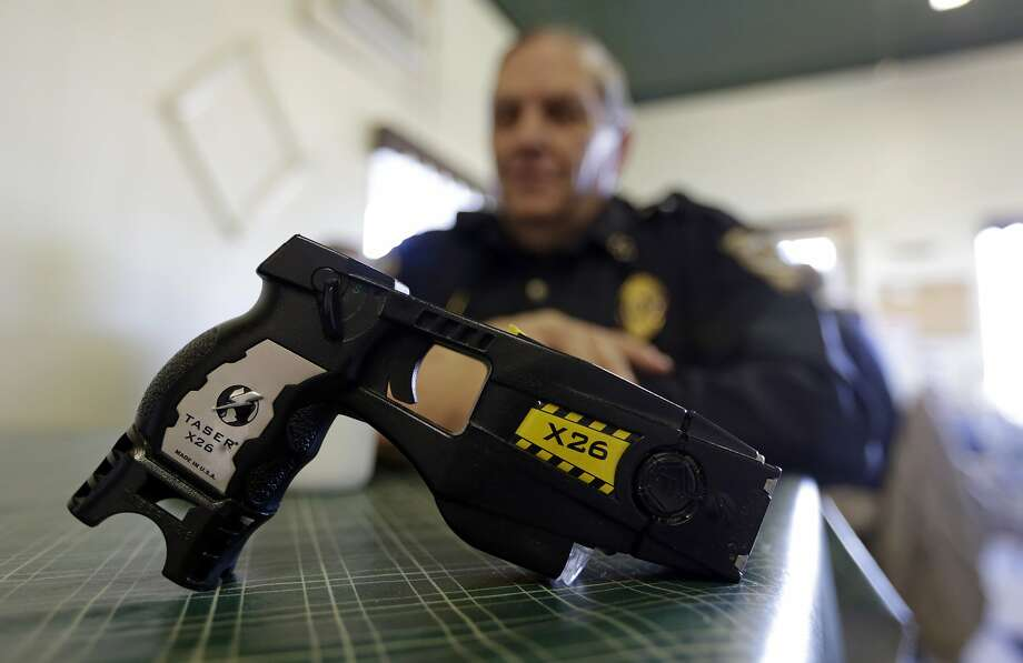 FILE - In this Nov. 14, 2013, file photo, a Taser X26 sits on a table in Knightstown, Ind. In the recent shootings of unarmed black men in a San Diego suburb and in Tulsa, Oklahoma, the police officers who fired the fatal shots were accompanied by officers who simultaneously drew their stun guns. Civil rights advocates say the different response by officers facing the same suspect and the same apparent threat illustrates a breakdown in police training and communication and shows that some officers are too quick to turn to deadly force.  (AP Photo/Michael Conroy, File) Photo: Michael Conroy, Associated Press