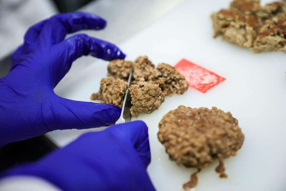 Scientist Mallory Mau cuts up a burger in the test kitchen at the Impossible Foods headquarters in Redwood City. Photo: Gabrielle Lurie, The Chronicle