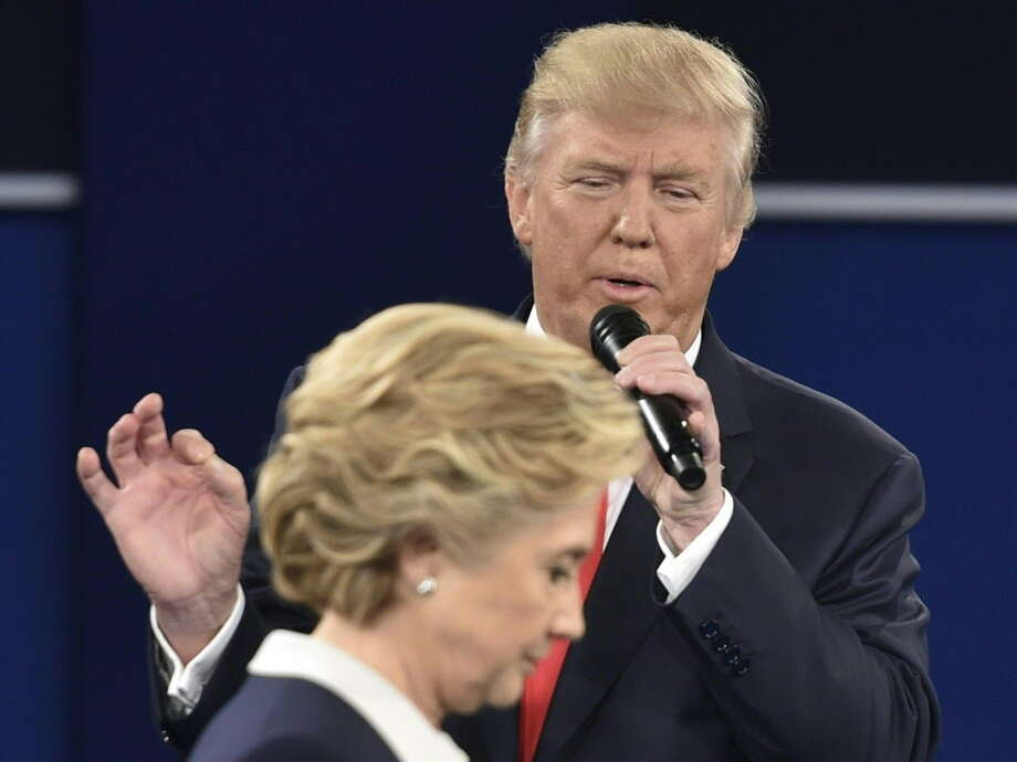 Republican presidential candidate Donald Trump speaks as Democratic presidential candidate Hillary Clinton walks past during the second presidential debate at Washington University in St. Louis, Missouri on October 9, 2016. Photo: PAUL J. RICHARDS / AFP or licensors