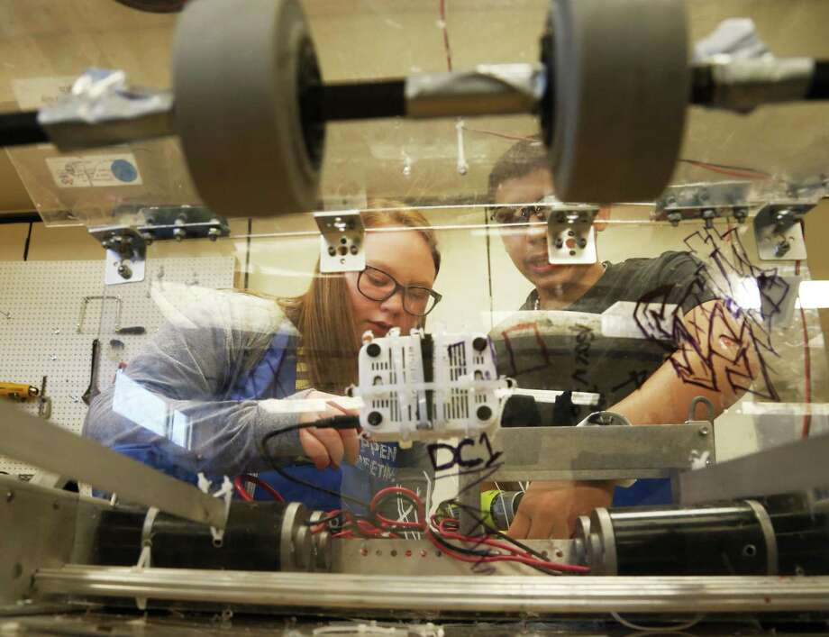 Carley Fell works with Robert Gonzales on the robotics projects at STEM Early College High School in 2016. STEM job growth in the field is getting higher, but Latinos aren't grasping the opportunities. Photo: Ron Cortes /