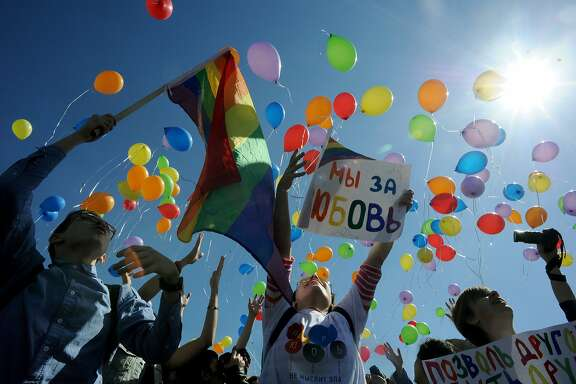 Gay rights activists release balloons as they take part in a flash mob devoted to the World Day Against Homophobia and Transphobia in St. Petersburg, on May 17, 2014. AFP PHOTO / OLGA MALTSEVA (Photo credit should read OLGA MALTSEVA/AFP/Getty Images)
