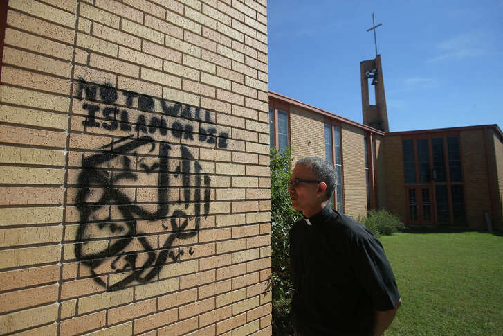 Pastor Eric Miletti (right) looks at graffiti Monday October 10, 2016 that was painted on a wall at Gethsemane Lutheran Church at 610 Avalon. Police are investigating the incident.