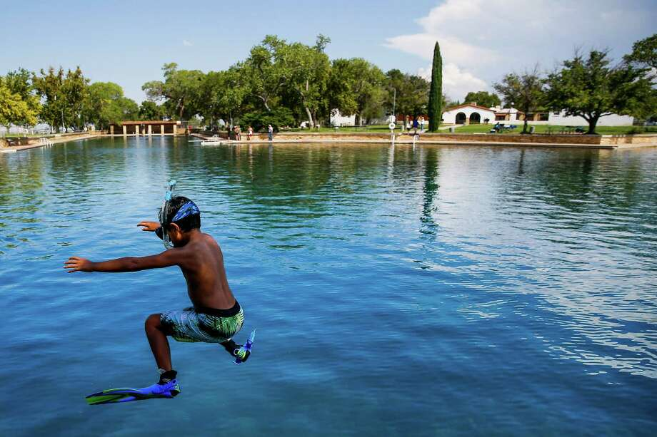Dean Strong, 8, jumps into the crystal-clear waters of the world's largest spring-fed swimming pool in Balmorhea State Park. Photo: Michael Ciaglo, Staff / © 2016  Houston Chronicle