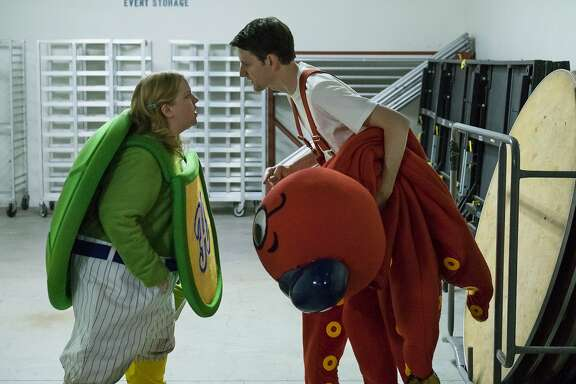 "This image released by Netflix shows Sarah Baker, left, and Zach Woods in a scene from ""Mascots."" (Scott Garfield/Netflix via AP)"